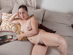 Liana poses naked on her beige sofa