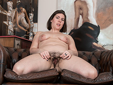 Sharlyn strips naked on her leather couch